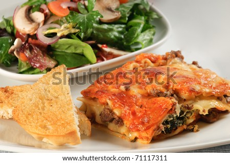 Gourmet Lasagna with chef salad and garlic toast - stock photo