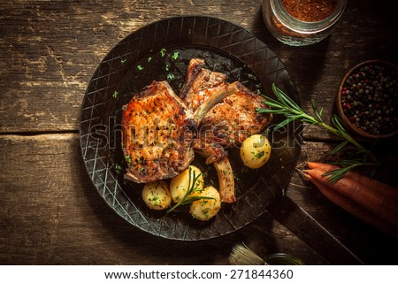 Gourmet meal of marinated pork cutlets served with boiled baby jacket potatoes seasoned with fresh herbs in an old frying pan on a rustic wooden kitchen table - stock photo
