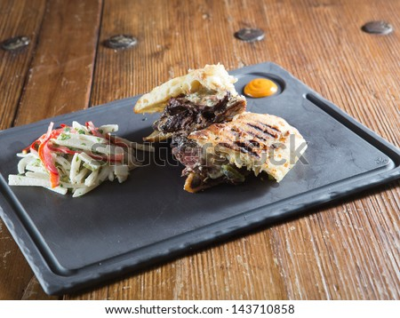 Gourmet medium-rare steak and Gorgonzola cheese grilled panini served with a red and green cabbage coleslaw on a cast iron plate with a honey mustard. - stock photo