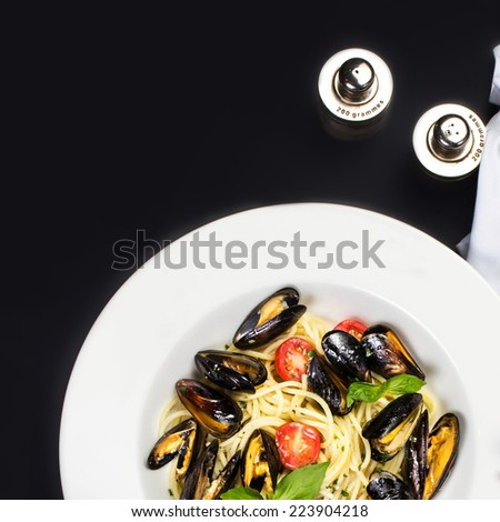 Gourmet mussels with fresh italian pasta, cherry tomato and herbs for a tasty seafood meal over black background, macro - stock photo