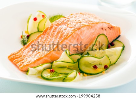 Gourmet oven-baked pink salmon steak served with thinly sliced cucumber as a delicious seafood starter to a dinner - stock photo
