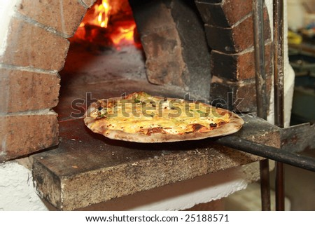 gourmet pizza coming out of wood fired pizza oven in restaurant