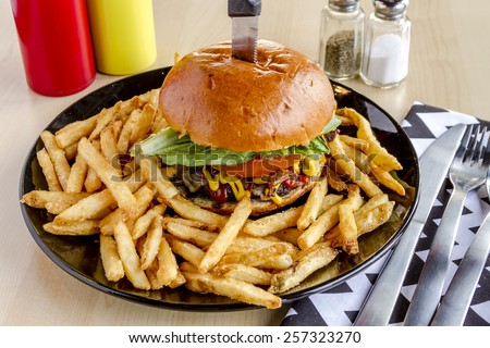 Gourmet pub hamburger with bacon on black plate with french fries sitting on wooden table - stock photo