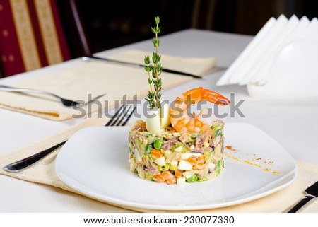 Gourmet seafood and vegetable appetizer with a mousse of chopped fresh vegetables and seafood topped with hard-boiled egg, herbs and a pink prawn plated and served at table - stock photo