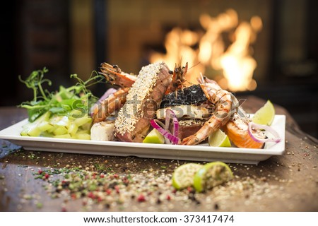 Gourmet seafood - Delicious grilled seafood platter with salmon, shrimp, tuna, lime and carambola fruit served on a wooden table, fireplace on background - stock photo