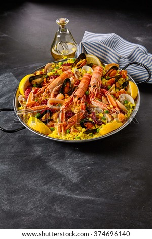 Gourmet seafood Valencia paella with fresh langoustine, clams, mussels and squid on savory saffron rice with peas and lemon slices, close up view - stock photo