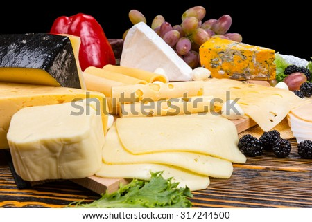 Gourmet selection of cheeses on a cheeseboard garnished with fresh blackberries, olives, grapes, and red bell pepper - stock photo