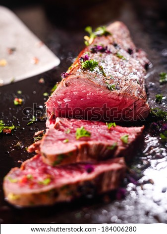 Gourmet sliced rare roast beef seasoned with chopped fresh herbs ready to be served for dinner - stock photo