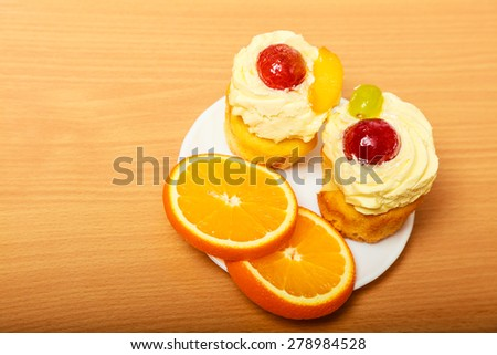 Gourmet tasty cookie cake with sweet cream and fruits as dessert food on top served with orange on plate.  - stock photo