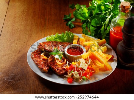 Gourmet Tasty Grilled Meat, Potato Fries, Fresh Veggies and White Cheese on White Plate with Sauce at the Center. Served on the Wooden Table. - stock photo
