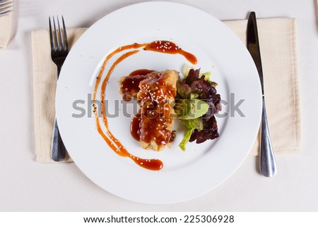 Gourmet Tasty Main Dish on White Round Plate with Utensils on Sides Served on White Table for the Guest at the Restaurant. - stock photo