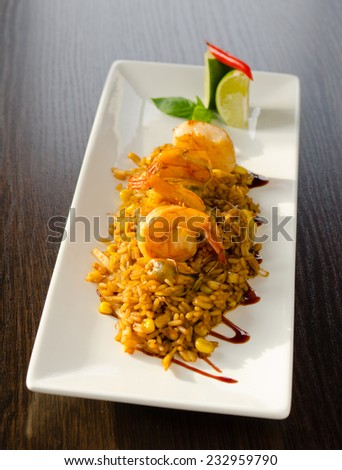 Gourmet Tasty Risotto Main Dish with Shrimp on Flavored Rice. Served on White Rectangular Plate at Wooden Table. - stock photo