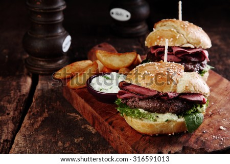 Gourmet Tasty Steak Burgers with Ham Slices on a Wooden Tray with Potato Wedges and Dipping Sauce.