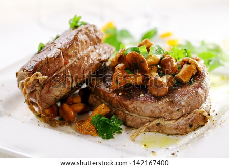 Gourmet thick juicy fillet steak medallions grilled to perfection and served topped with fried wild mushrooms and herbs - stock photo