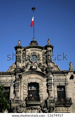 Government Palace with Clock Tower and Flag, Guadalajara, Mexico  This is a very old Spanish style building. - stock photo