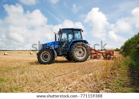 Gower, UK: August 05, 2014: Tractor in a field with bales of hay.