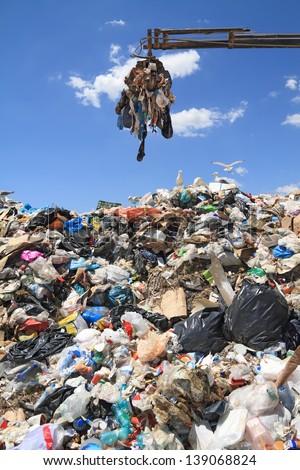 Grabber crane working in landfill - stock photo