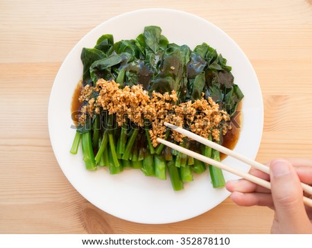 Grabbing Kale fried in oyster sauce with chopsticks. - stock photo