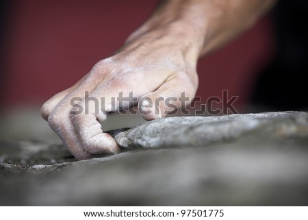 Grabbing onto a small handhold, a climber makes his way to the top. His hand is covered in chalk, and there is a very shallow depth of field. - stock photo