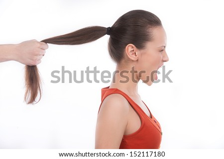 Grabbing the hair. Side view of furious young woman shouting while someone grabbing her hair - stock photo