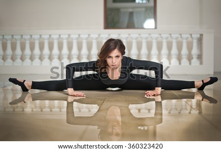 Graceful ballerina doing the splits on the marble floor. Gorgeous ballet dancer performing a split on glossy floor. Short hair young brunette in tight fit ballet outfit making her exercises. - stock photo