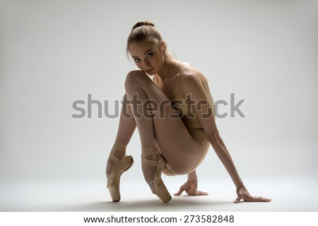 Graceful ballerina in a solid swimsuit sitting - stock photo