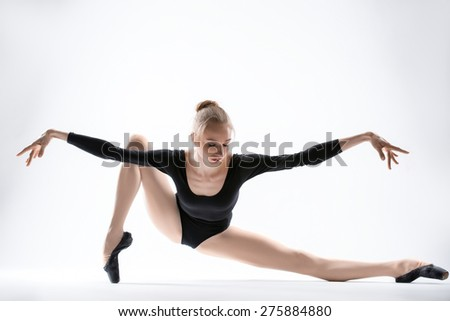 Graceful ballerina in black leotard doing stretching. Isolate on a white background in the studio. - stock photo