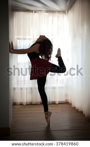 Graceful ballerina silhouette  in ballet pose. Gorgeous ballet dancer performing, on pointes. Ballerina making her exercises, indoors, surrounded by large windows with white transparent curtains . - stock photo