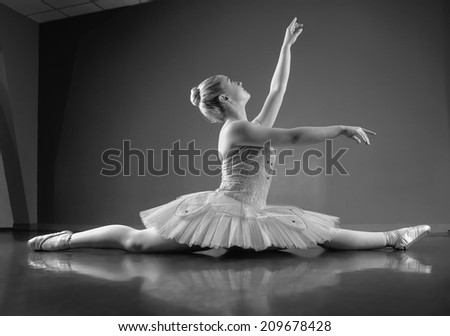 Graceful ballerina sitting with legs stretched out in the ballet studio - stock photo
