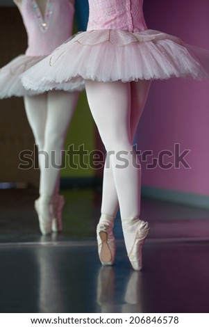 Graceful ballerina standing en pointe in front of mirror in the ballet studio - stock photo