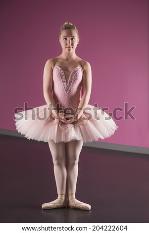 Graceful ballerina standing in first position in the ballet studio - stock photo