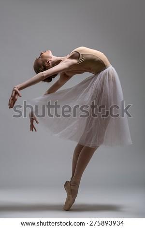 Graceful ballerina standing on toes bending the back. Studio shot. - stock photo