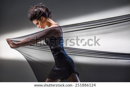 Graceful brunette stretches stretch mesh fabric in front of you on the background of bright ray of light in the studio. Fashion photography. The girl in a dark dress short. - stock photo