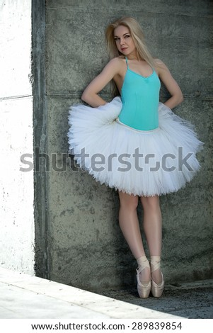 Graceful dancer with blond hair on the background of gray concre - stock photo