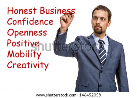 graceful entrepreneur describes the basic principles of doing business / attractive man in an expensive suit writing the words of a red marker - isolated on white background