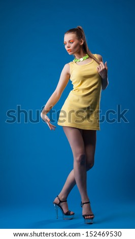 Graceful girl posing with disco makeup in studio - stock photo