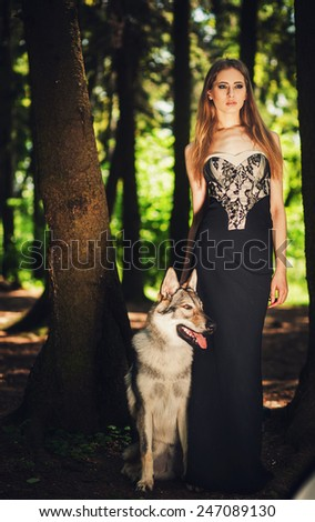 graceful girl standing with a dog in summer forest - stock photo