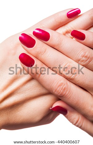 Graceful hands of a woman with red painted manicured nails in a close up view isolated on white