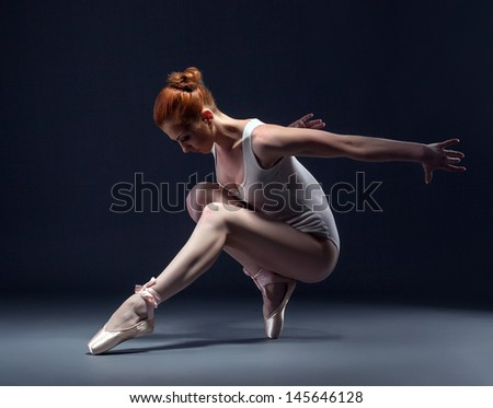 Graceful slender ballerina dancing in studio - stock photo