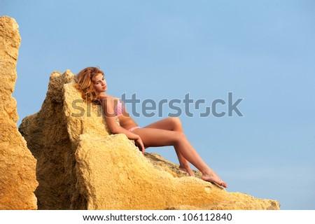 Graceful young woman in bikini lying on the yellow rock - stock photo