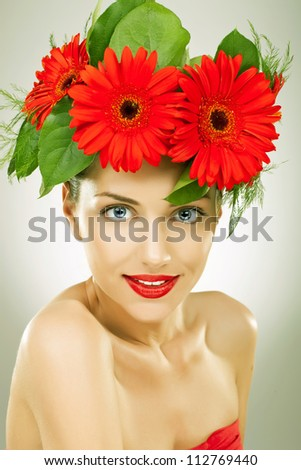 gracefull young woman with red gerbera flowers in her hair looking and smiling to the camera - vintage picture style
