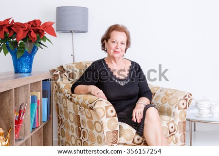 Gracious elegant senior woman relaxing at home in a comfortable armchair sitting smiling at the camera, festive red poinsettia flowers in a vase - stock photo
