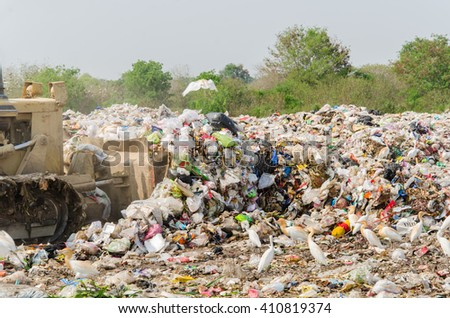Grade loader running landfill waste. The birds are looking for food. - stock photo