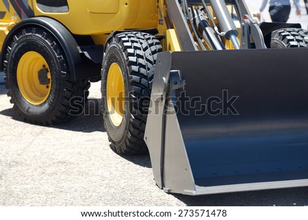 Grader staying on the road. Fragment of machine - stock photo