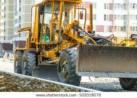 Grader working outside on road construction in summer