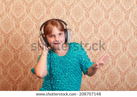 Gradeschool girl at home listening to music on a pair of vintage 1970s wired headphones - stock photo