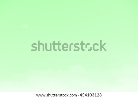 Gradient of green color, soft color gradient of fluffy cloud and half moon on a day light sky background, use for business presentation background or desktop wallpaper - stock photo