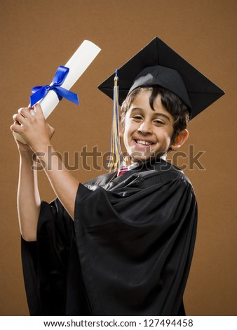 Graduate boy with mortarboard holding his diploma - stock photo