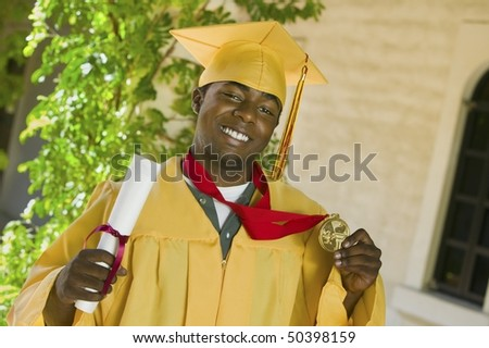 Graduate holding diploma and medal outside, portrait