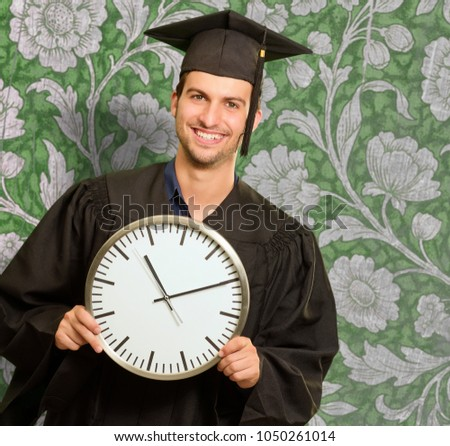 Graduate Man Holding Clock Against Wallpaper